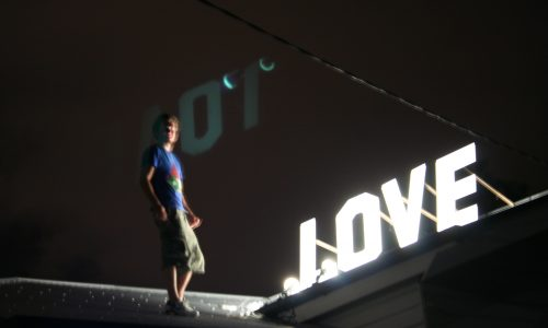 IMAGES DOCUMENTATION EXHIBITIONS FRIENDS 7 : Steve on roof at Annie St with his work 'Love' (in preparation for group exhibition Renovare)